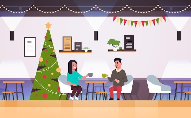 コーヒーを飲みながらカフェのテーブルに座って、メリークリスマス幸せな新年の休日のコンセプトモダンなレストランのインテリアとの会議中に話し合うカップル