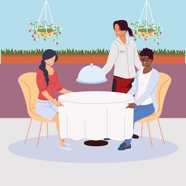 Пара сидит за столом в ресторане, обслуживает официантка