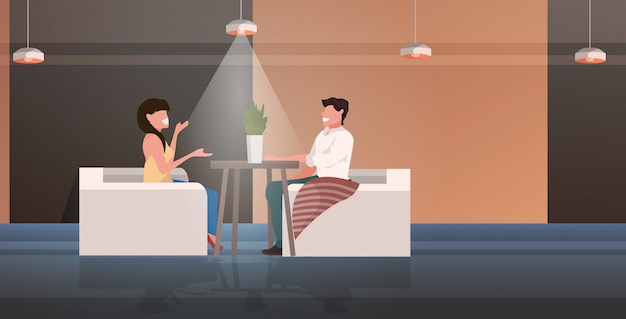 Couple sitting at cafe table discussing during meeting romantic date