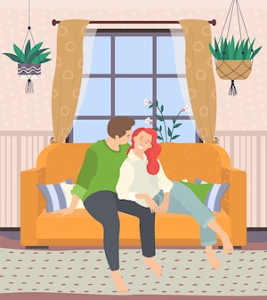 Couple sitting on couch in living room at home
