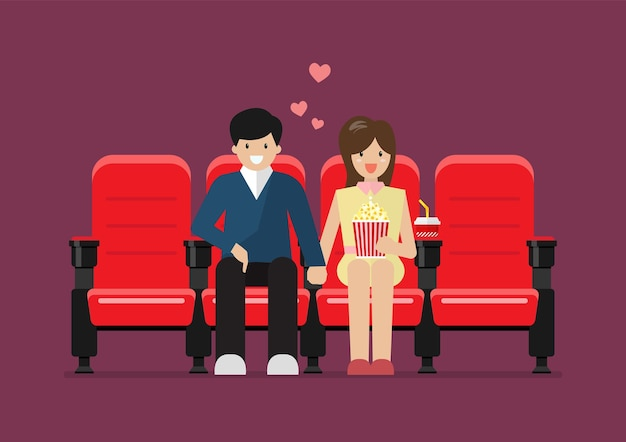 Couple sitting on red cinema chairs with popcorn and drink in movie theater.
