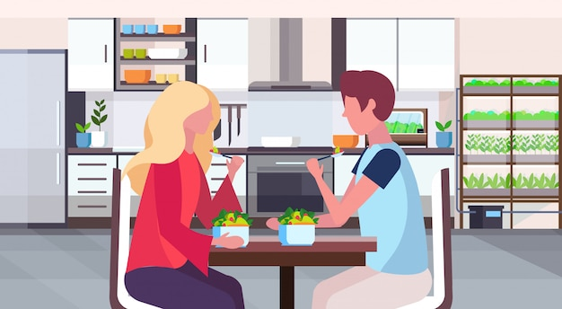 Couple sitting at table man woman eating fresh fruits salad healthy food concept modern home room with smart plants growing system kitchen interior flat horizontal portrait