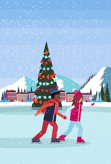 Couple skating in ice rink with decorated christmas tree at ski resort hotel