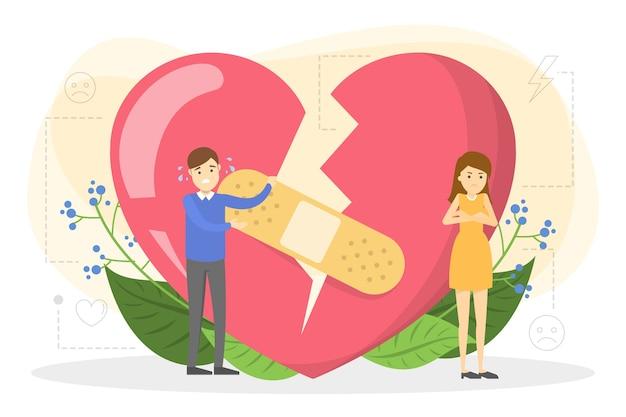 Пара, стоящая у большого красного разбитого сердца.