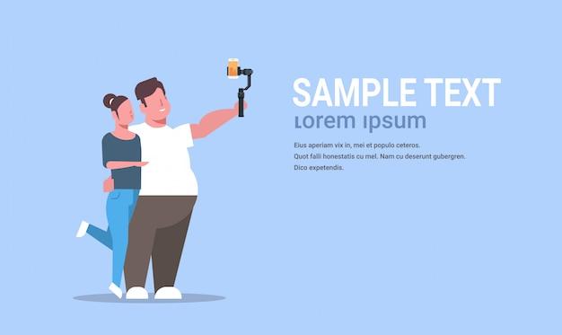 スマートフォンで写真を撮るselfieスティックを保持している薄い女性とカップルが一緒に立っている男