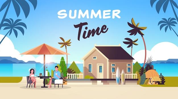 カップルの夏の休暇の男性女性がサンライズビーチヴィラの家熱帯の島でワインの傘を飲む