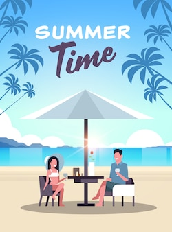 Couple summer vacation man woman drink wine umbrella on sunrise beach tropical island vertical