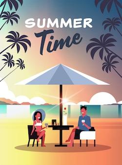 Couple summer vacation man woman drink wine umbrella on sunset beach tropical island vertical