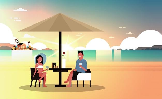 Couple summer vacation man woman drink wine umbrella on sunset beach villa house tropical island