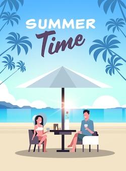 Couple summer vacation man and woman drinking wine, umbrella on sunrise beach tropical island vertical flat