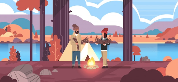 Couple tourists hikers holding firewood man woman organizing fire near camp tent hiking camping concept autumn landscape nature river mountains