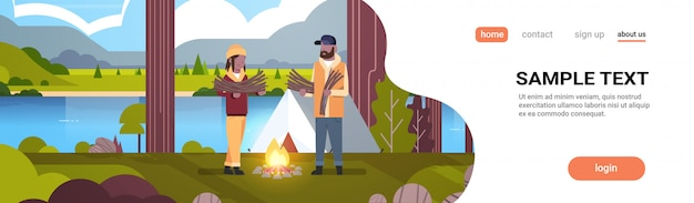Couple tourists hikers holding firewood  man woman organizing fire near camp tent hiking camping concept landscape nature river mountains background horizontal full length copy space