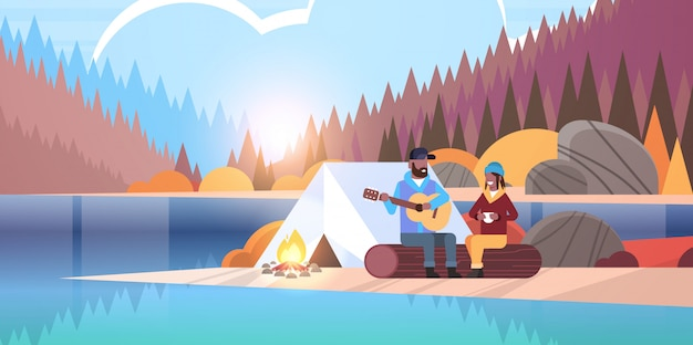 Couple tourists hikers relaxing in camp  man playing guitar for girlfriend sitting on log hiking concept sunrise autumn landscape nature river forest mountains background horizontal