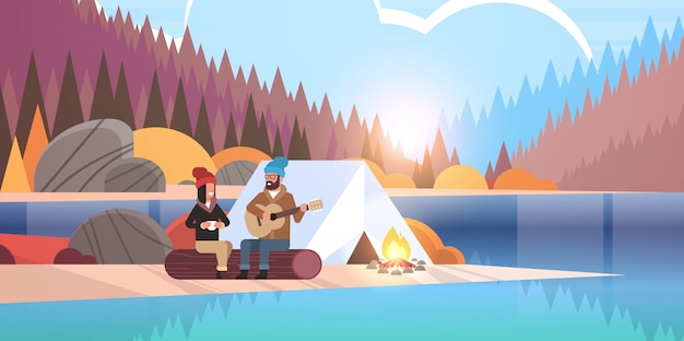 Couple tourists hikers relaxing in camp man playing guitar for girlfriend sitting on log hiking concept sunrise autumn landscape nature river forest mountains