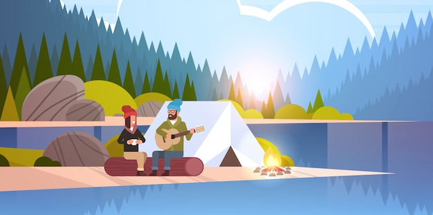 Couple tourists hikers relaxing in camp man playing guitar for girlfriend sitting on log hiking concept sunrise landscape nature river forest mountains