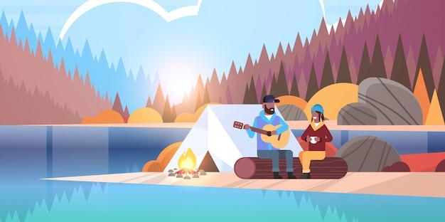 カップル観光客ハイカーキャンプ男でリラックスしたログハイキングコンセプト日の出秋の風景自然川森林山背景水平に座っているガールフレンドのギターを弾く
