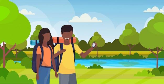 Ключевые слова на русском: пара туристы туристы с использованием компас поиск направление пешие прогулки концепция мужчина женщина афро-американских путешественников на поход река пейзаж фон горизонтальный плоский категории:.