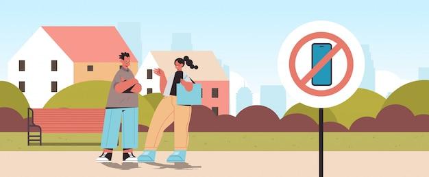 カップルが都市公園を歩いている携帯電話ゾーンのデジタルデトックスコンセプトスマートフォンで禁止標識
