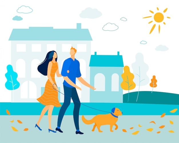秋の都市公園で犬と一緒に歩くカップル