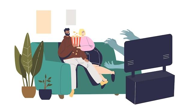 自宅でテレビで映画を見ているカップルがソファに怯えて座っている