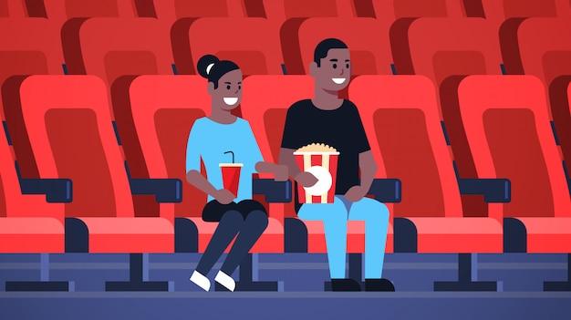 ポップコーンとコーラのアフリカ系アメリカ人男性の女性が日付を持っていると新しいコメディフラット全長水平で笑いながら映画に座って映画を見てカップル