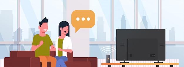 スマートスピーカー音声認識を使用してソファに座っているテレビの男性女性を見てカップルがアクティブ化されたデジタルアシスタントのコンセプトモダンなリビングルームのインテリアフラット水平肖像画