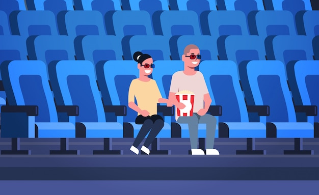 Couple wearing 3d glasses watching movie sitting in cinema with popcorn and cola man woman having date and laughing at new comedy flat full length horizontal