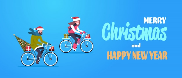 Couple woman man riding bike with fir tree gift box in christmas