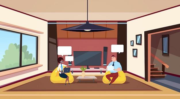 現代のリビングルームで豆袋の椅子に座っているコンピューターで作業するカップル
