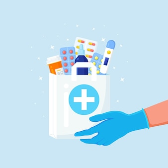 Courier hands in disposable gloves hold paper bag with pills bottle, medicines, thermometer inside.