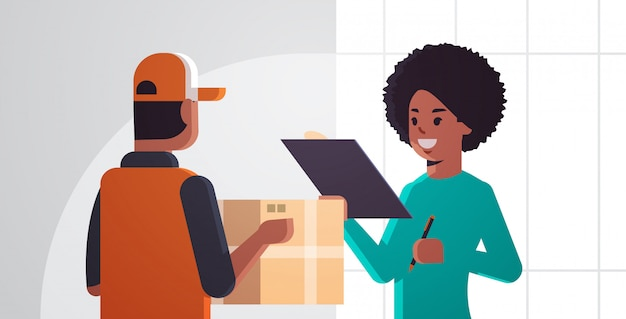Courier man delivering cardboard parcel box to african american woman recipient express delivery service concept girl holding document to signing signature horizontal portrait
