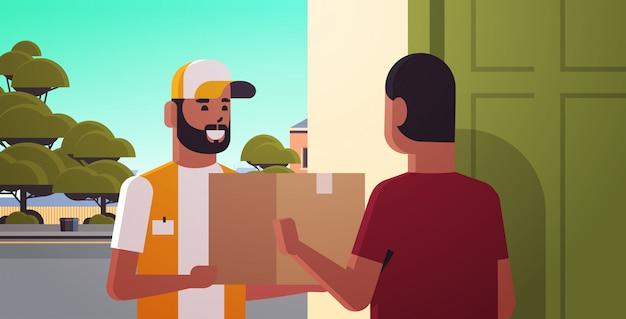 Человек курьера поставляя картонную коробку пакета к афро-американскому парню получателю на дому концепция службы экспресс-доставки горизонтальная портрет