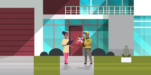 Курьер мужчина дарит букет цветов женщине получателю экспресс-служба доставки концепция девушка получает посылку от доставщика современное здание экстерьер горизонтальный полная длина