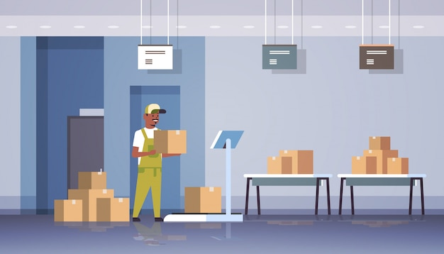 Courier man in uniform putting parcel box on scales mail express delivery logistic service concept modern warehouse interior  horizontal full length