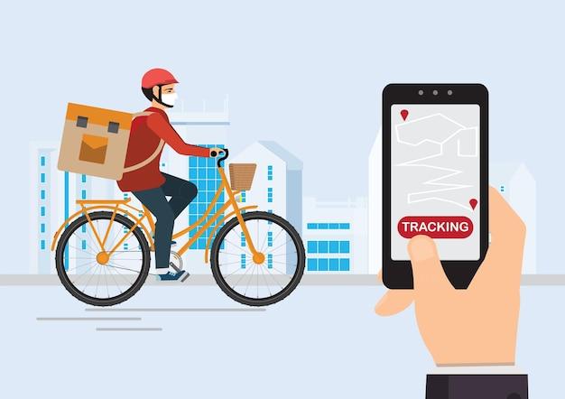 뒷면에 소포 상자가있는 자전거 택배가 자신의 스마트 폰을 사용하여 주문을 추적하고, 백그라운드에서 도시 거리, 물류 및 기술, 스마트 폰의 배달 서비스 앱