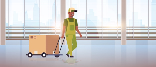 Courier in uniform pushing trolley with cardboard box express delivery service concept   worker with hand truck modern office hall interior  full length horizontal