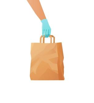 식료품과 종이 에코 가방을 들고 택배 장갑을 낀 손. 음식 배달 개념.