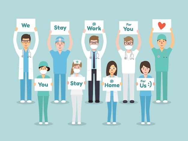 Врачи, медсестры и медицинский персонал держат плакат с просьбой, чтобы люди избегали распространения вируса короны и covid-19, оставаясь дома.