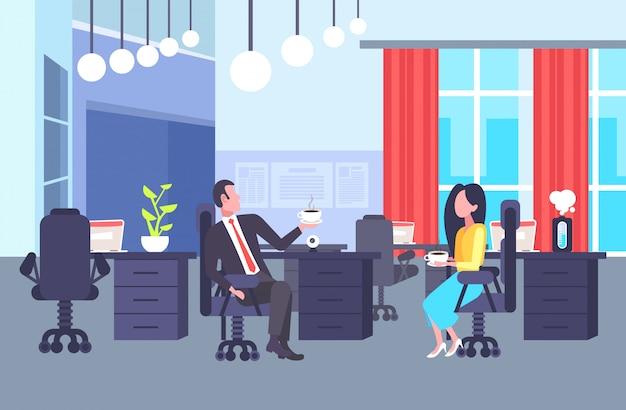 同僚のカップルがコーヒーブレーク中に一緒に議論する職場の同僚に座っている男性女性ビジネス人々オフィスコワーキングセンターインテリア水平全長