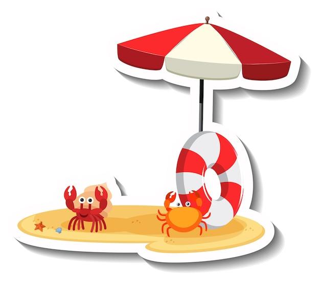 비치 파라솔과 수영 반지와 함께 모래에 게