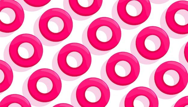 白い背景で泳ぐためのピンクのゴム円の創造的な組成パターン。トップビュー、フラットレイアウト