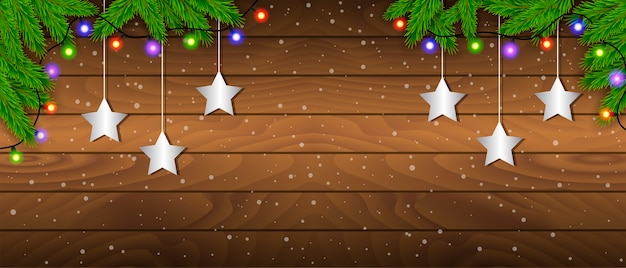 Creative frame made of christmas fir branches on wooden background with christmas lights. xmas and new year theme