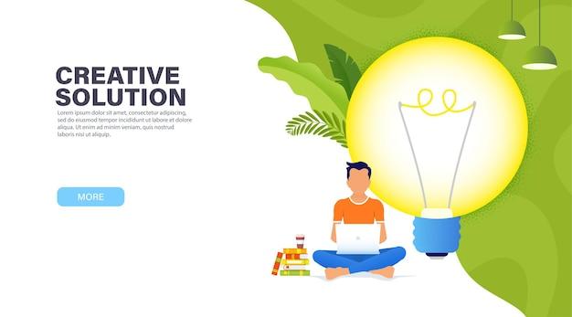 Концепция творческого решения. парень сидит в позе лотоса с ноутбуком возле большой светящейся лампочки и работает над новой творческой идеей.