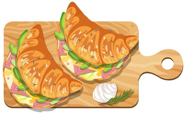 木の板にハムチーズが入ったクロワッサンサンドイッチ