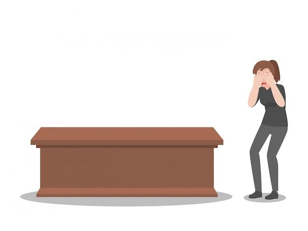 教会での葬式で棺を持つ女性を泣いて