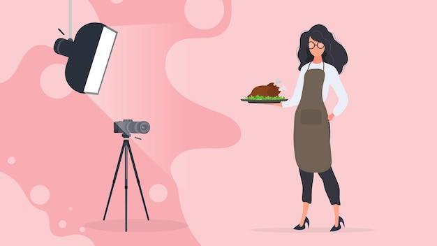 요리 블로거. 주방 앞치마를 입은 여성이 쟁반에 프라이드 치킨을 들고 있습니다. 삼각대에 카메라, 소프트박스. 요리 블로그 또는 vlog의 개념입니다. 벡터.
