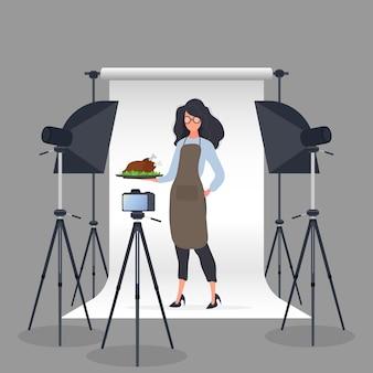요리 블로거. 주방 앞치마를 입은 여성이 쟁반에 프라이드 치킨을 들고 있습니다.