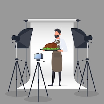 Culinary blogger. a man in a kitchen apron holds a fried chicken on a tray. camera on a tripod, softbox. culinary blog or vlog concept. vector.