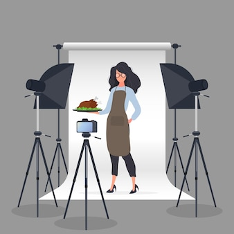 Culinary blogger. a woman in a kitchen apron holds a fried chicken on a tray.