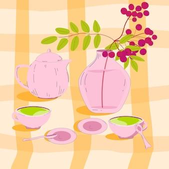 テーブルクロスの上にお茶とナナカマドの果実の花瓶があります